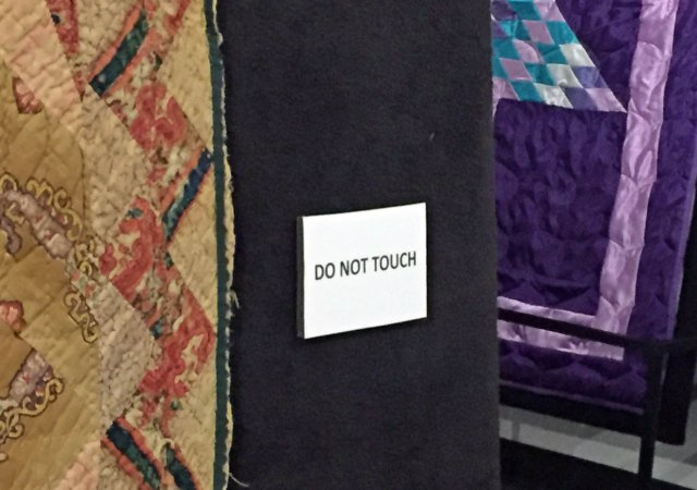 Taken at the Nebraska History Museum in a quilt exhibit. Quilts are displayed on slant boards with stanchions but are otherwise out in the open. Each slant board has one of these Do Not Touch signs.